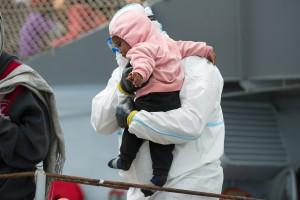Un operatore umanitario accoglie una bambina immigrata appena sbarcata sulle coste della Sicilia