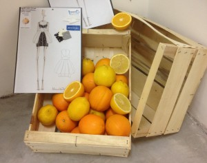 Una cassetta di agrumi con il bozzetto di un abito Orange Fiber