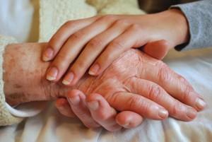 La mano di un anziano e la mano di una badante