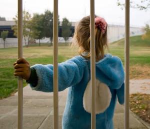 Una bambina di spalle con delle sbarre