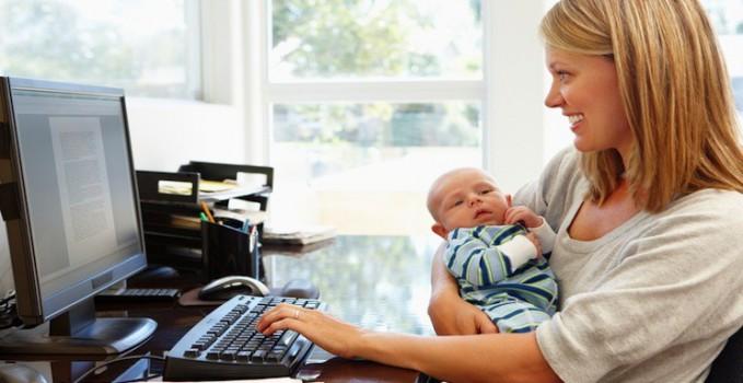 Una mamma che lavora al computer con un neonato in braccio
