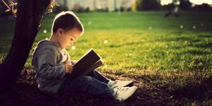 bimbo che legge sotto un albero